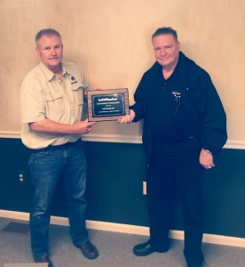 Piercy Woods, LiftMaster Representative, presents Award of Excellence plaque to Joe Karp, Micrologic Sales Engineer.